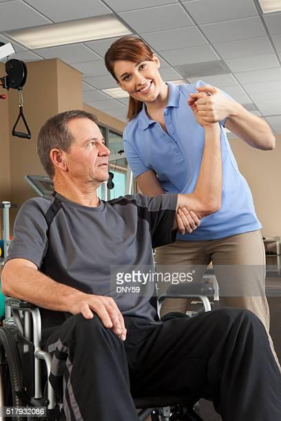 Physiotherapeutin bewertet Bewegungsfreiheit von Patienten im Rollstuhl