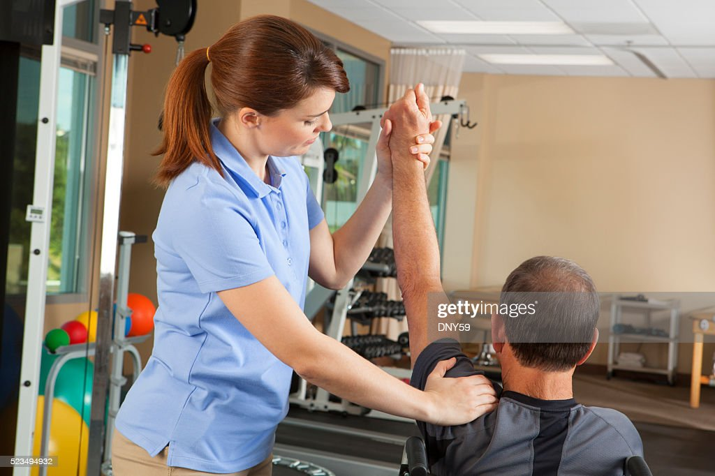 Fisioterapista valutazione libertà di movimento del paziente in sedia a rotelle : Foto stock