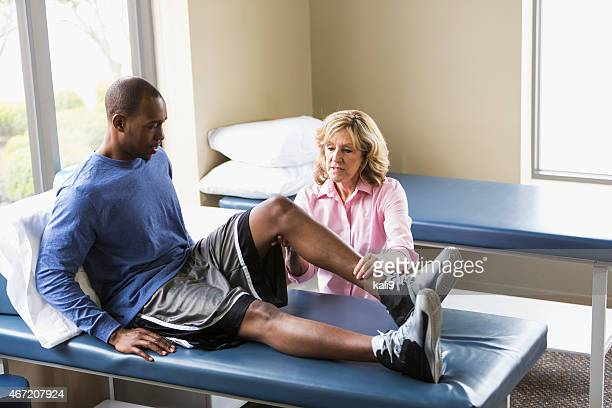 Physical therapist examining patient