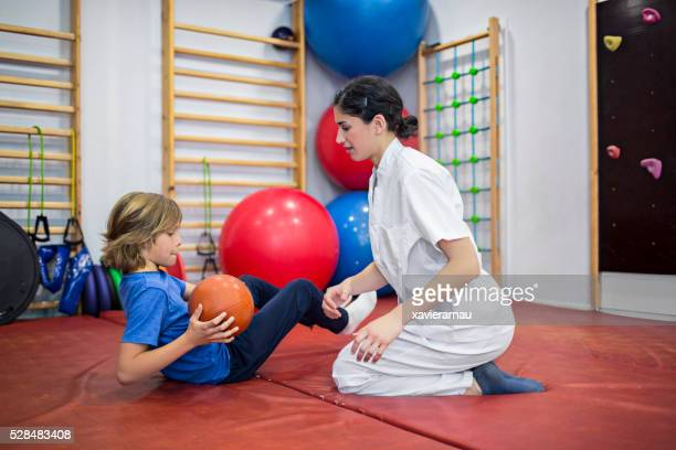 Physical therapist guiding child holding medicine ball
