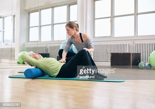 Physical therapist helping elder woman at gym : Stock Photo