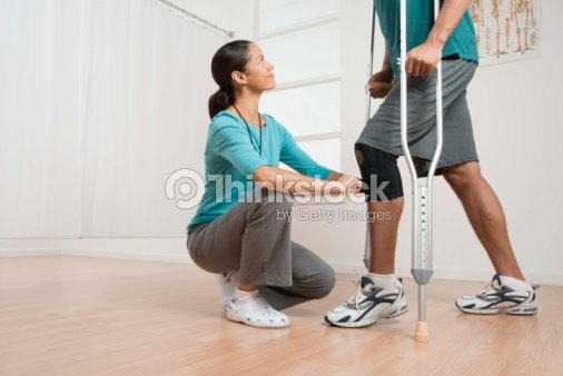 Physical therapist helping patient with crutches : Stock Photo