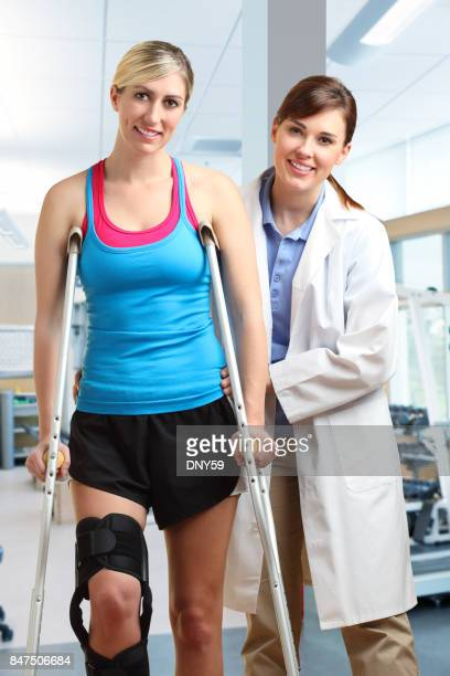 Physical Therapist Helping Patient With Use Of Crutches