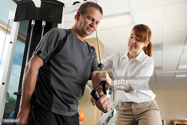 Physical therapist instructing man on proper use of exercise equipment