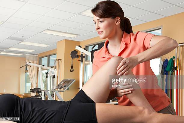 Physical therapist manipulating the knee of a female patient