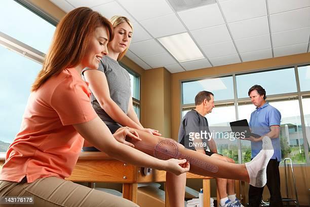 Physiotherapeutin messen eine weibliche Patienten's mit gestrecktem Knie