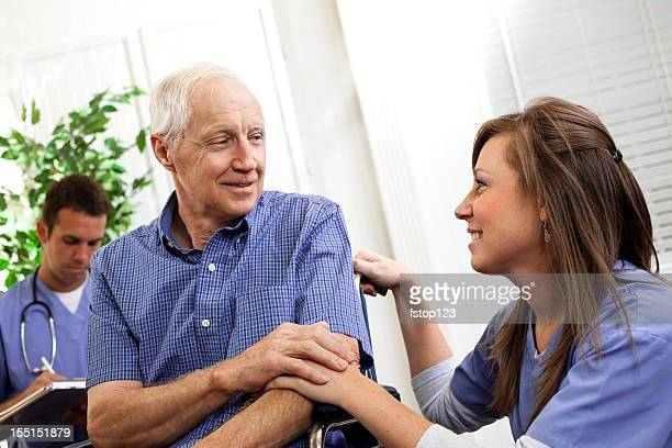Physical therapist or nurse consoling senior man patient. Wheelchair. Doctor.