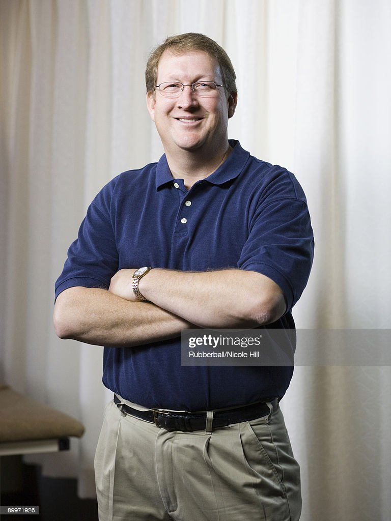 physical therapist standing with arms folded