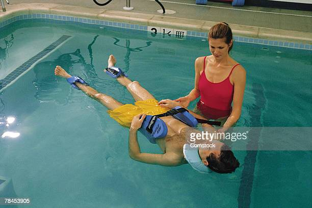Physical therapist with patient in pool