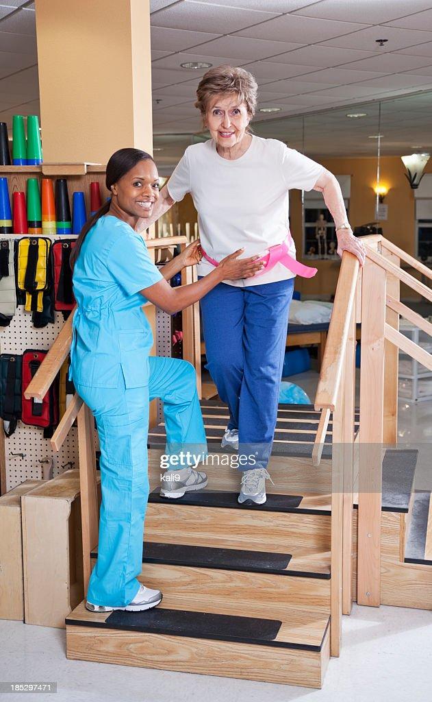 Fisioterapista con donna anziana fare le scale : Foto stock