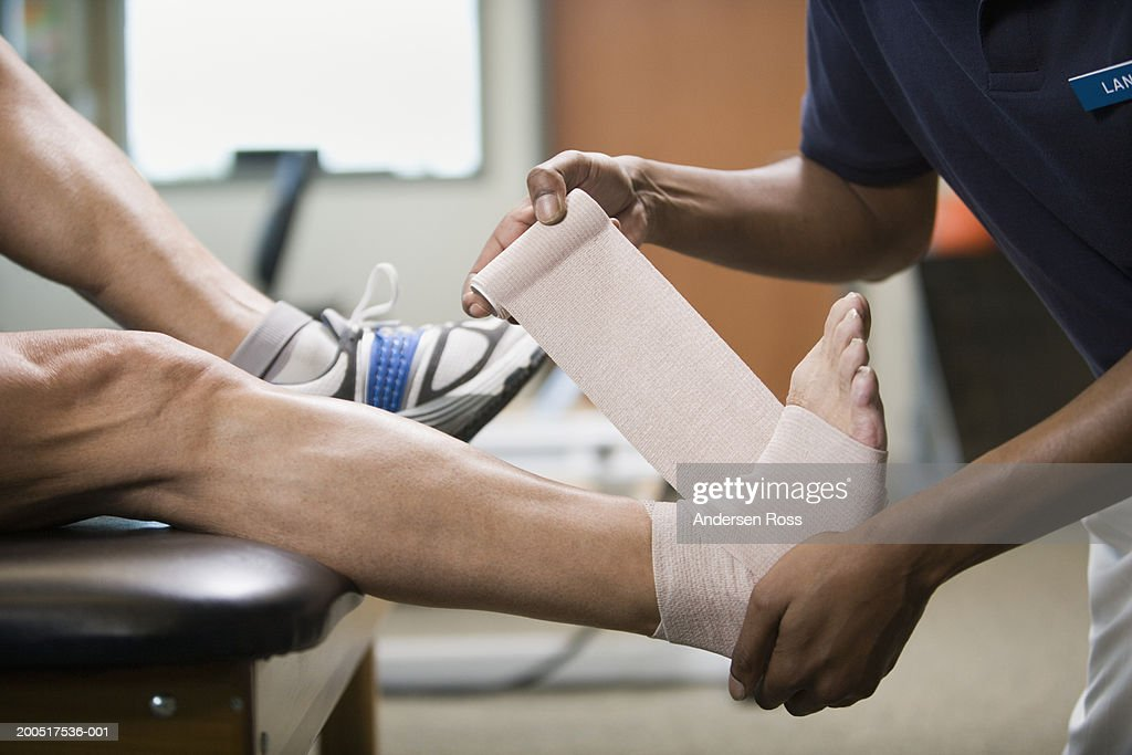 Physical therapist wrapping mature man's foot in bandage, side view : Stock Photo
