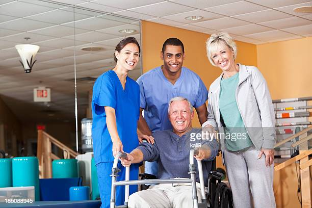 Physical therapists with patient and spouse