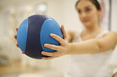 Brunette woman on physical therapy. Focus on ball.