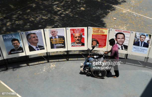 A physically challenged elderly IndoFrench citizen is transported on a wheelchair by an assistant past a display of portraits of French presidential...