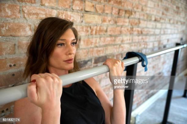 Femme physiquement apte faire une traction vers le haut dans la Barre