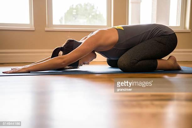 Körperlich Passen junge Frau üben Yoga Garbhasana Wohnzimmer