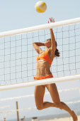 Physically Fit Young Woman Spiking Volleyball