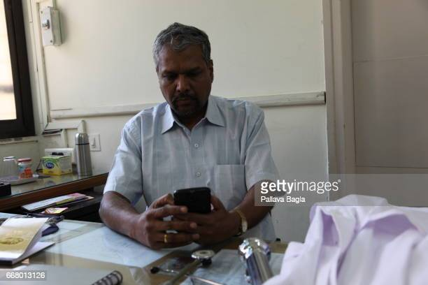 Physician Hemant Haldavnekar examines a tele ECG received on his mobile phone on March 4 2017 in Mumbai India A credit card sized lifesaving electro...