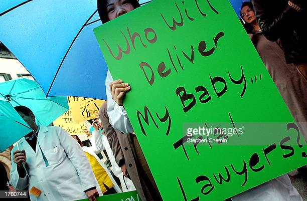 A physician holds a protest sign at a rally at the New Jersey Capitol Complex February 4 2003 in Trenton New Jersey About 3000 health care workers...
