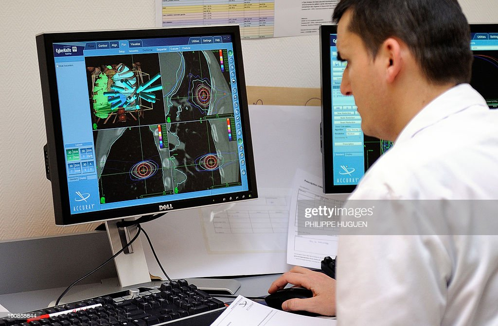 A physician looks at a screen as a patient undergoes a Cyberknife treatment, on February 6, 2013, at the Oscar Lambret Center in Lille, northern France, a regional medical unit specialised in cancer's treatment. HUGUEN