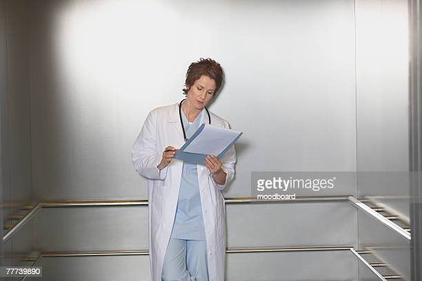Physician Making Notes in Patients Chart