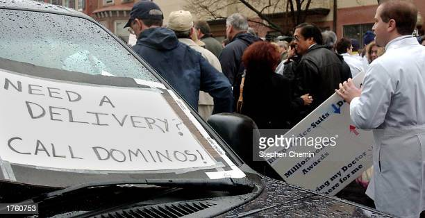 Physicians walk by a sign that reads 'Need A Delivery Call Dominoes' posted on a car as they leave a rally at the New Jersey Capitol Complex February...