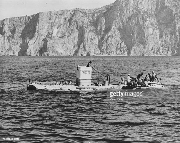 Physicist Auguste Piccard and his son Jacques Piccard are part of a crew boarding a rowing boat after surfacing in the bathysphere 'Trieste'...