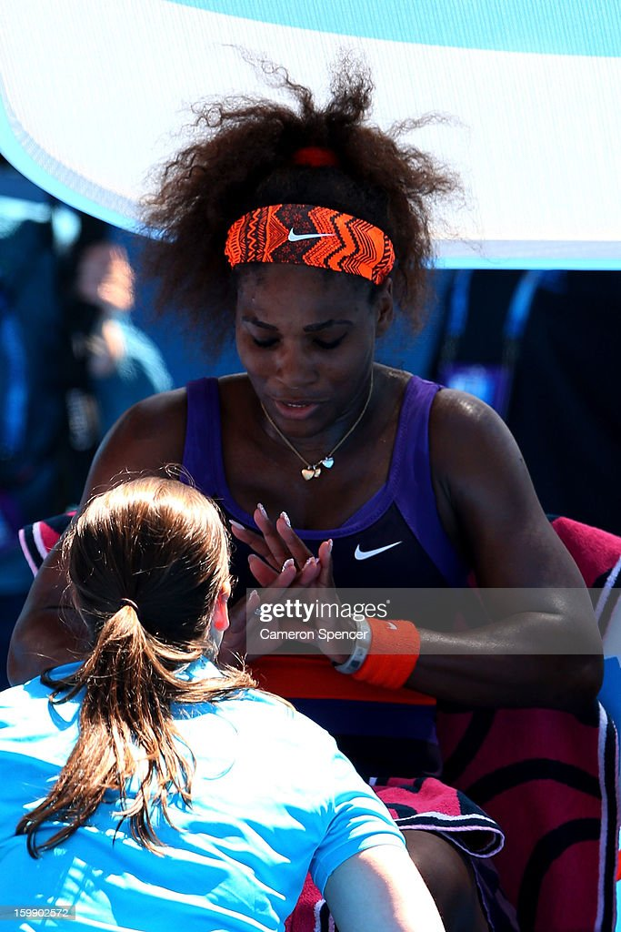 A physio attends to Serena Williams of the United States of America during an injury time out in her Quarterfinal match against Sloane Stephens of the United States of America during day ten of the 2013 Australian Open at Melbourne Park on January 23, 2013 in Melbourne, Australia.