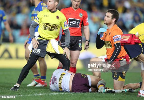 A physio signals to the bench following an injury to Andrew McCullough of the Broncos during the round 21 NRL match between the Parramatta Eels and...