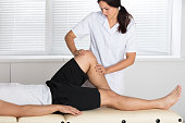 Young Female Physiotherapist Giving Leg Exercise To Patient In Clinic