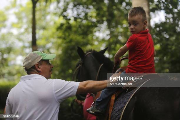 Physiotherapist Gustavo Vallejo accompanies a child as he rides a horse during his hippotherapy session in Matagalpa town some 130 kilometres from...