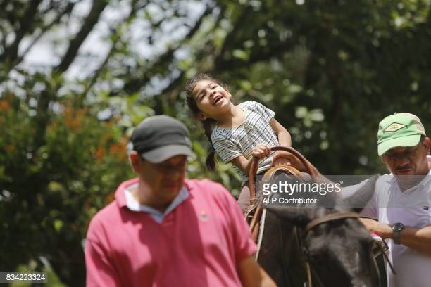 Physiotherapist Gustavo Vallejo accompanies little Allison Espinoza as she rides a horse during her hippotherapy session in Matagalpa town some 130...