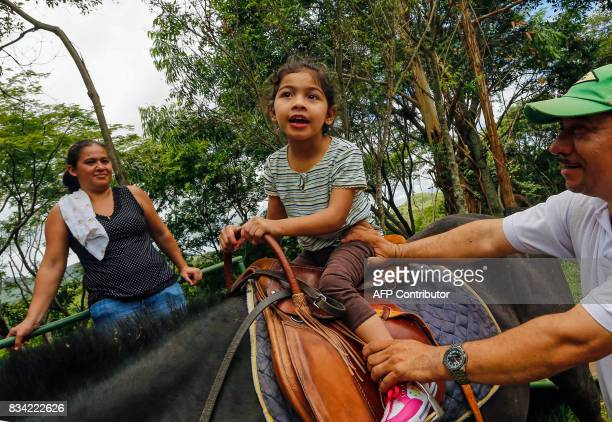 Physiotherapist Gustavo Vallejo prepares little Allison Espinoza for her hippotherapy session in Matagalpa town some 130 kilometres from Managua on...