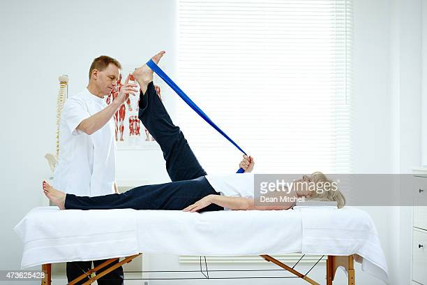 Physiotherapist helping his patient stretching in medical office