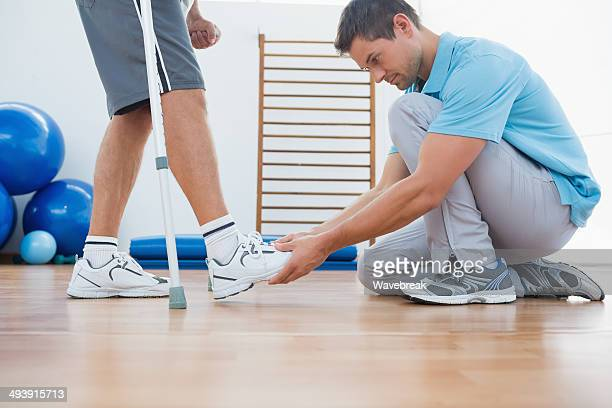Physiotherapist helping man with crutches