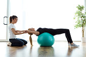Shot of physiotherapist helping patient to do exercise on fitness ball in physio room.