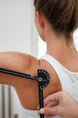 Physiotherapist measuring shoulder flexion with goniometer
