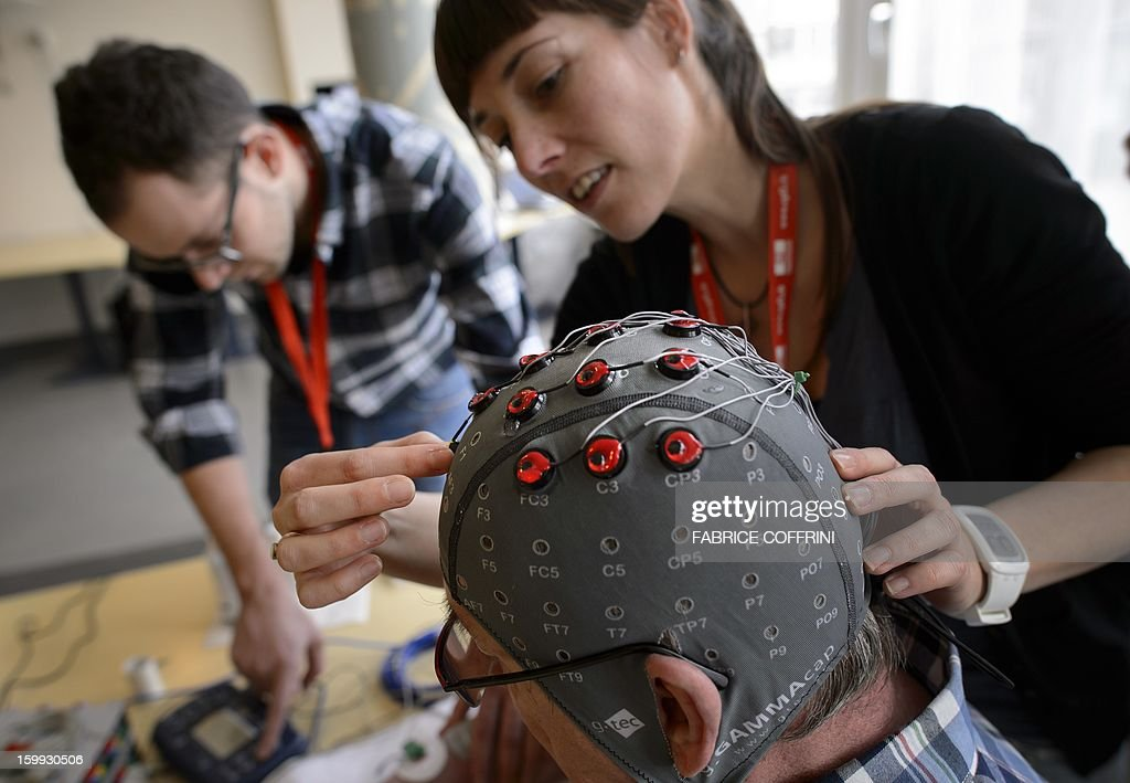 Physiotherapist Vanessa Buhlmann places electrodes on the head of patient Jean-Francois Vernetti during a presentation of a brain-machine interface by the Swiss Federal Institutes of Technology of Lausanne (EPFL) on January 23, 2013 in Sion. More than one hundred patients suffering from severe motor impairments have voluntarily participated in the development of non-invasive brain-machine interfaces. The main purpose of TOBI Eiuropean research program is to allow the patients either regain some of their mobility or improve their social relationships.
