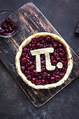 Pi Day Cherry Pie - making homemade traditional Cherry Pie with Pi sign for March 14th holiday, on rustic background, top view.
