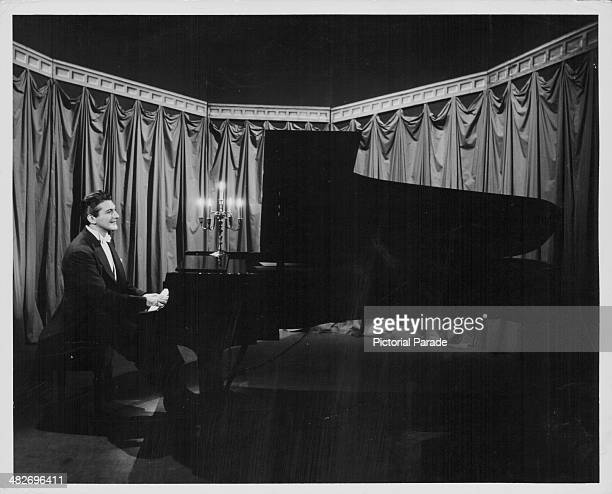 Pianist Liberace performing on a candle lit stage circa 1950