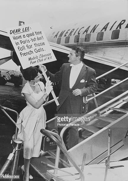 Pianist Liberace posing with a member of his fan club as he boards a flight to Paris circa 1955