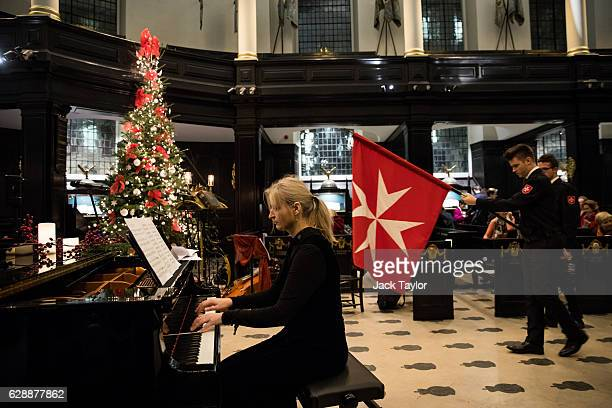 A pianist plays as an Order of Malta Cadet carries a flag during an AngloPolish Carol Service at the St Clement Danes Church on December 9 2016 in...