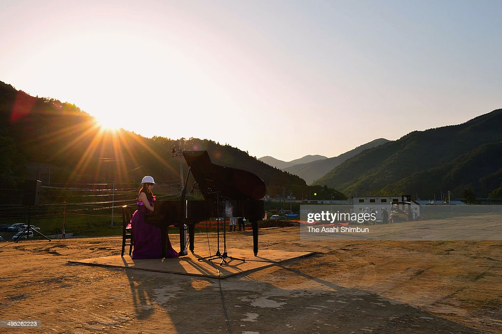 A pianist plays the grand piano which had been damaged by the subsequent tsunami of the magnitude 9.0 earthquake in 2011, on the 11-meter-high new seawall on June 1, 2014 in Kamaishi, Iwate, Japan. The piano was returned to Toni Elementary School after getting repaired.