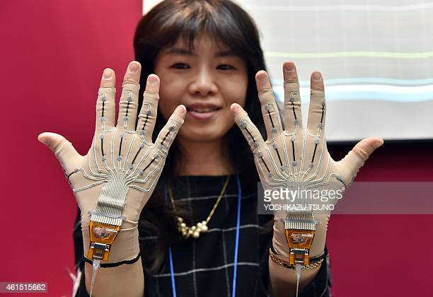 A pianist wears special gloves with motion sensors that record fingerwork of players at the Wearable Device Technology Expo in Tokyo on January 14...
