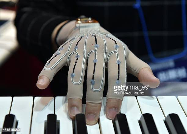 A pianist wears special gloves with motion sensors that record the fingerwork of players at the Wearable Device Technology Expo in Tokyo on January...
