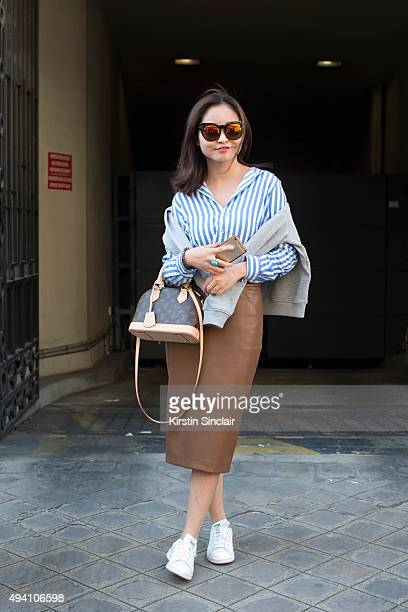 Pianist Wen Yao wears a Carven sweater Zara top and shoes Louis Vuitton bag Zara skirt and Quay sunglasses on day 3 during Paris Fashion Week...
