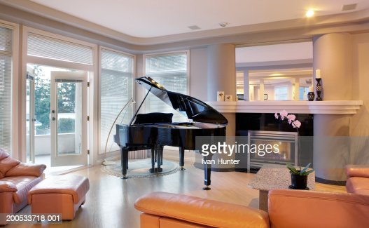 Piano Beside Fireplace In Living Room Stock Photo