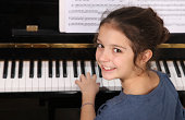 Young girl seated in front of a piano keyboard