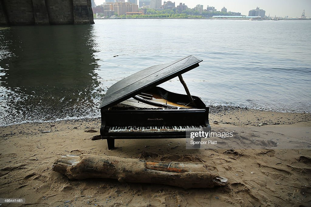 A piano sits underneath the Brooklyn Bridge on June 3, 2014 in New York City. A grand piano that has mysteriously landed on a sliver of beach under the iconic bridge last week has become an impromptu tourist attraction. While the Mason & Hamlin piano is badly damaged, dozens of people climb onto the beach daily to test out the keys.
