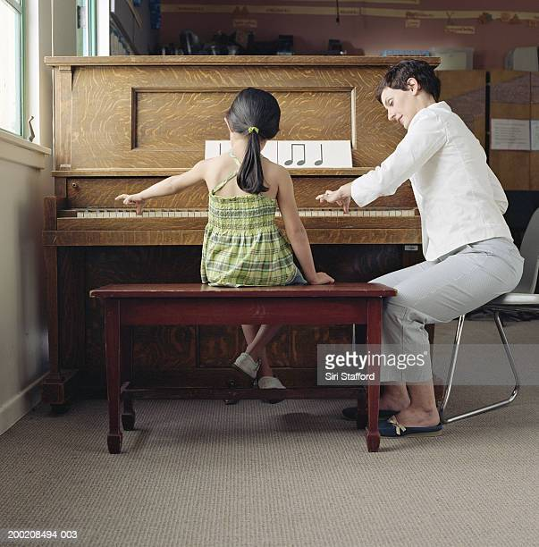 Piano teacher working with student (4-6) at piano